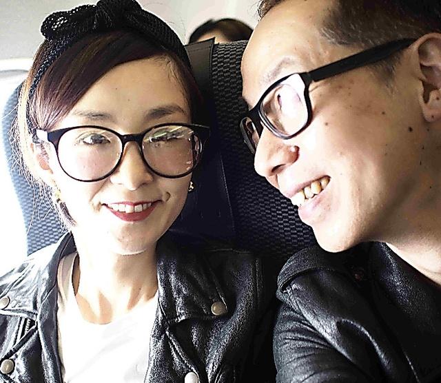 菊地貴公さん(右)、奈穂美さん。最初の手術の半年後、福岡旅行に向かう飛行機で=2014年5月