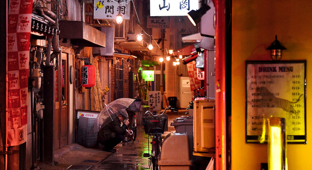 飲み屋街の細い路地裏で開店を待つ男性。明かりがともると同時に店に消えた=高知市