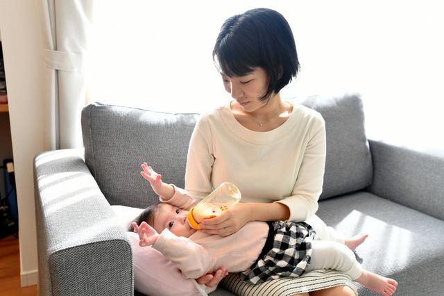 消毒した哺乳瓶を使ってミルクを娘に飲ませる母親=2018年11月14日、広島市、小川智撮影