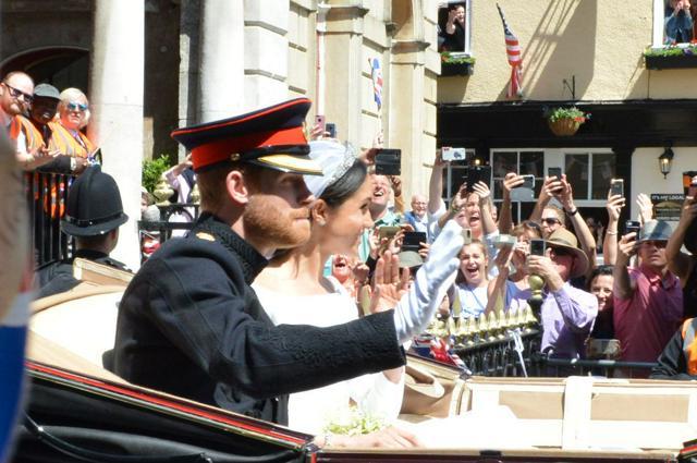 結婚式を挙げ沿道の歓声に応える、英王室ハリー王子とメーガン妃=2018年5月19日、ウィンザー