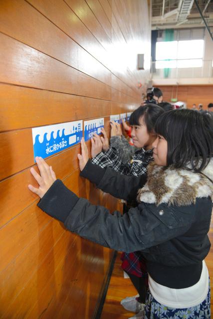 水害時の浸水の高さを示すシールを貼って高さを実感する小学生たち=大阪市西成区の北津守小学校、宮崎勇作撮影