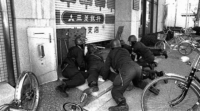 シャッターのすき間から銀行内部の様子をうかがう機動隊員=1979年1月26日、大阪市住吉区