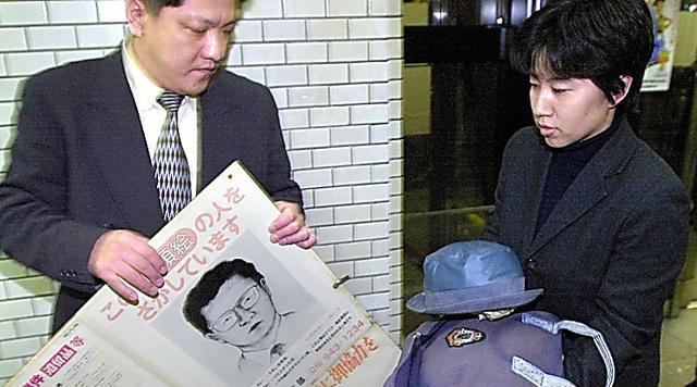 グリコ・森永事件は2000年2月13日午前0時に最終時効が成立。似顔絵のポスターなどを撤去する署員ら=大阪市中央区の南署