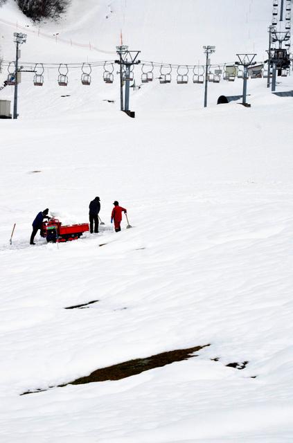 ゲレンデを整備する係員。ところどころ土がのぞいていた=23日、長岡市栖吉町の市営スキー場