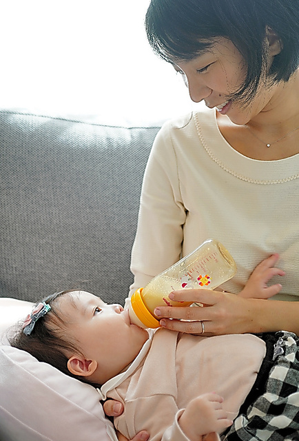 消毒した哺乳瓶に入れたミルクを娘に飲ませる母親=小川智撮影