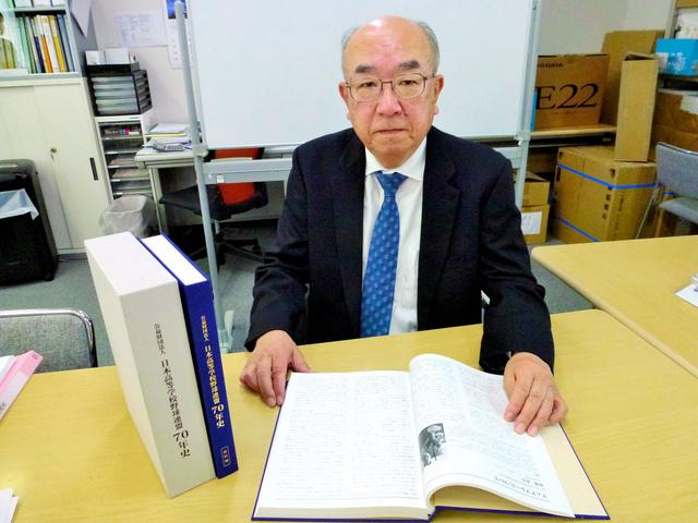 日本高等学校野球連盟70年史をめくる田名部和裕さん