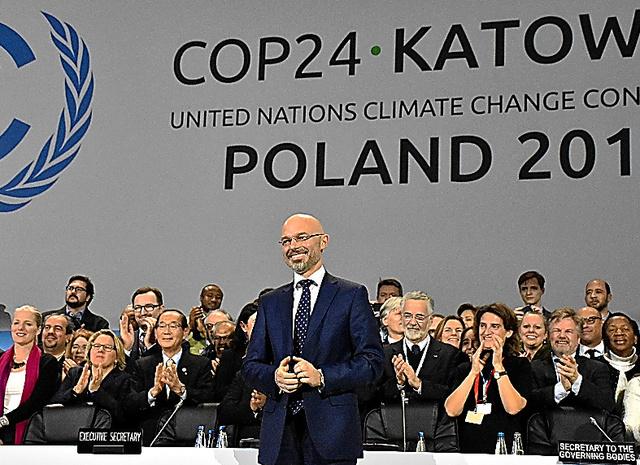 パリ協定の運用ルールの採択を祝うCOP24議長のポーランドのクリティカ環境副大臣(中央)と各国閣僚ら
