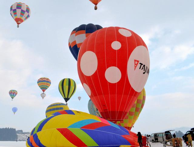 次々に舞い上がる熱気球=小千谷市内の西中会場