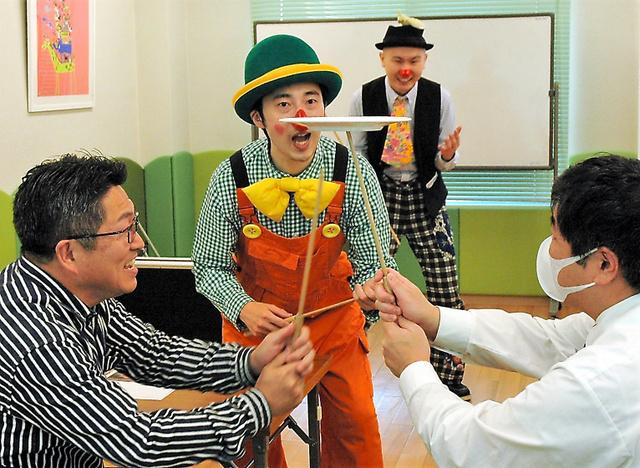 報告会の参加者を巻き込んで皿回しを演じるクラウンの「まろ」さんと「ケンケン」さん(奥)=鹿児島市西田1丁目