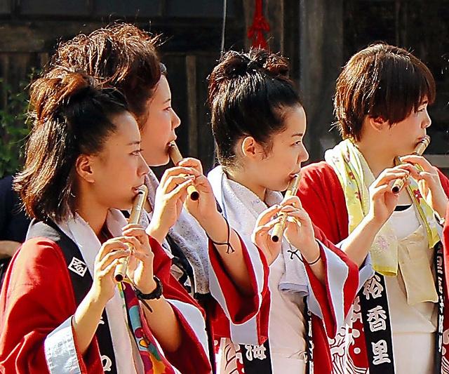 祭りで笛を吹く安部薫さん(右端)ら明治学院大生=2014年、岩手県大槌町