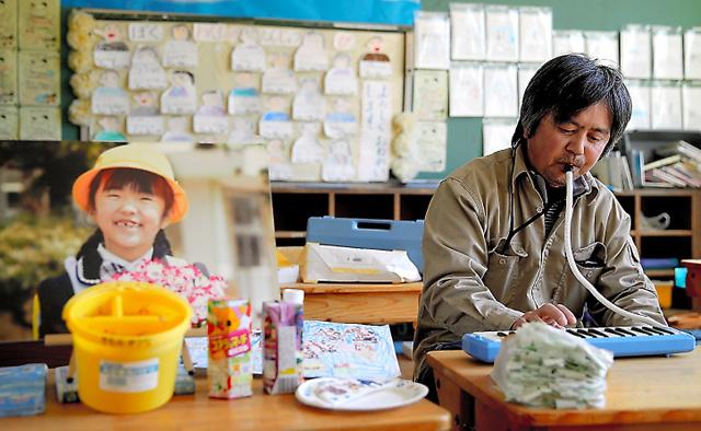 汐凪ちゃんが通った小学校の教室に写真を飾り、鍵盤ハーモニカを演奏する木村紀夫さん=福島県大熊町、三浦英之撮影