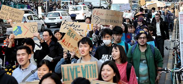 地球温暖化の危機を訴えるため、デモ行進する参加者=15日午後、東京都渋谷区