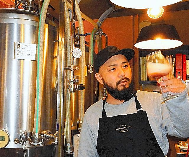 ビールの醸造装置と鍛島悠作さん=熊本市