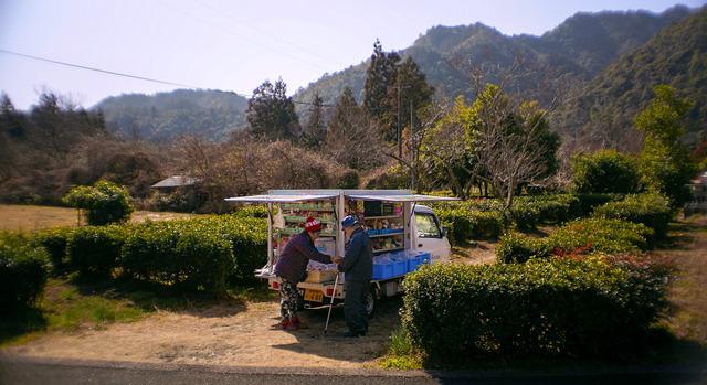生鮮品を満載したJ笑門が集落に着いた。お店を開いた赤い帽子の山下渥子さん(左)に、鈴木利久さんが歩み寄った=愛知県新城市