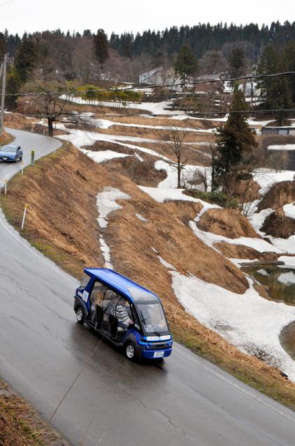 雪が残る棚田の脇を走っていく自動運転の電動カート。車幅は133センチと軽自動車より15センチほど狭い=21日、長岡市山古志地域