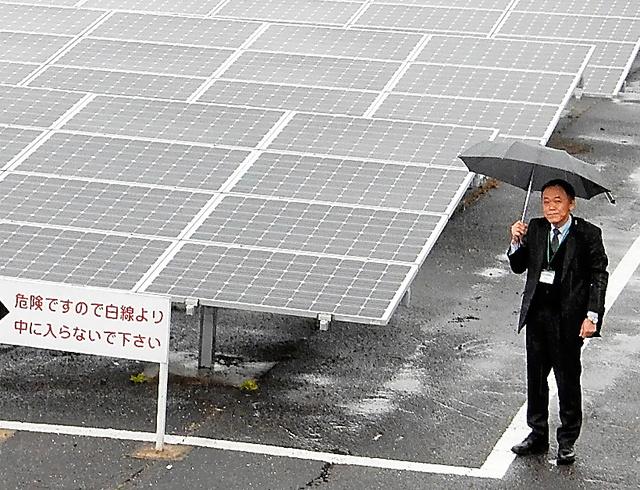 グリーン・市民電力の神在太陽光発電所と大橋年徳さん=福岡県糸島市