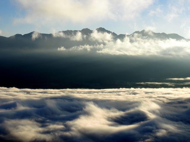 海のように波打つ雲。雲は空気の状態を私たちに教えてくれる。後方は八ケ岳(猪熊隆之さん提供)