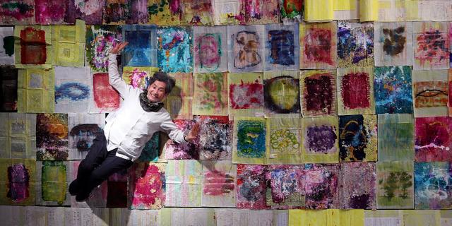 詩人の吉増剛造さん。敷き詰めた作品は極小文字の上に彩色したもので個展で展示された=12日、東京都中央区