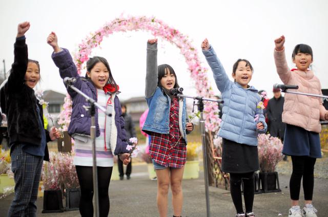 片手を上げてシーズンの開始を宣言する渡利小の児童ら=福島市の花見山公園