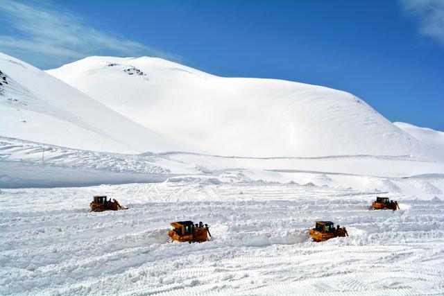6メートルを超す積雪がある室堂ターミナルの駐車場の除雪作業。ブルドーザーが列をなして雪を押し出している=2019年4月5日午前11時20分、富山県立山町、近藤幸夫撮影