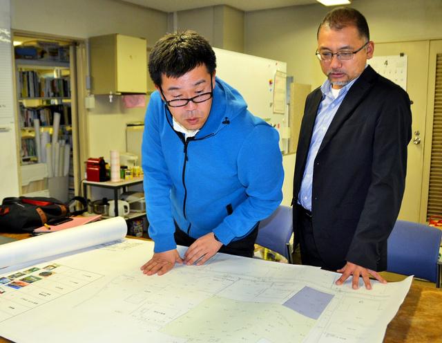 被災地域の地図を広げて議論する佐々木康彦さん(中央)と、柴田祐教授=2019年4月1日、熊本市の熊本県立大