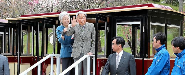 「こどもの国」の園内バス「あかポッポ号」に乗り込み、出迎えの人たちに手を振る天皇、皇后両陛下=2019年4月12日午前