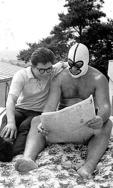 取材で写真撮影の際、門馬忠雄さん(左)と仲良く新聞を読むザ・デストロイヤーさん=1965年、長野県松本市、門馬さん提供