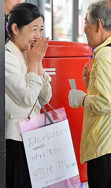 当選した翌朝も駅前に立ち、祝福される成田千尋さん(左)=22日午前6時58分、JR三鷹駅前