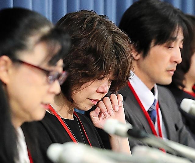 会見で、涙をぬぐう遺族(中央)=22日、東京・霞が関の文部科学省
