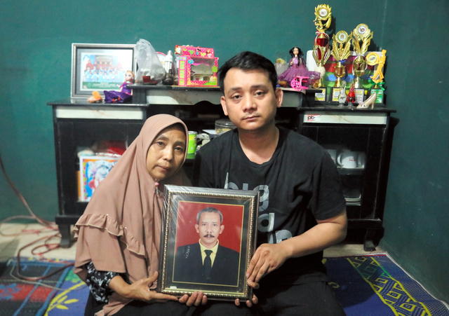 インドネシア大統領選の開票作業後に急逝したダヌ・ルダノさんの遺影を手にする妻のナニ・ヌルザナさん(左)と長男のトマ・スガラさん=2019年4月24日、ワルキドゥル村、野上英文撮影