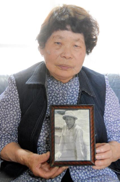 落雷で亡くなった調査員の田代成澄さんの遺影を持つ母親の信子さん=佐賀県神埼市