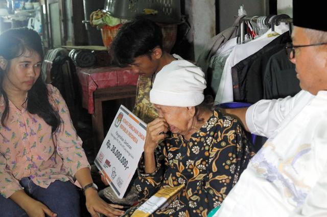 選挙作業での過労死で選挙管理委員長(右)から見舞金を受け取り、涙を浮かべる遺族=2019年5月3日、ジャカルタ、野上英文撮影