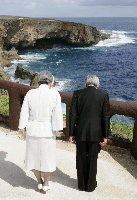 サイパンのプンタン・サバネタ(バンザイクリフ)の断崖と紺碧(こんぺき)の波が砕ける海に向かって、黙礼する平成の天皇と皇后=2005年6月28日