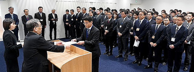 地元での業務再開初日を迎え、渡辺利綱町長(左)から辞令交付を受ける職員たち=7日、福島県大熊町