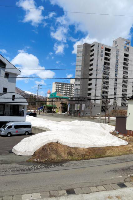 かつてマンション苗場が立っていた更地には雪が残っていた。右奥は運営会社が経営破綻(はたん)した会員制リゾートホテル=2019年4月15日、新潟県湯沢町三国、松浦新撮影