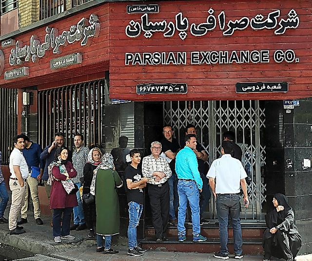 8日、テヘラン市内の通貨両替店で、現地通貨リアルを米ドルやユーロに両替しようと列をつくる人々。米の核合意離脱後の制裁でイランの経済苦境は深刻化し、現地通貨リアルは下落が続いている=AP