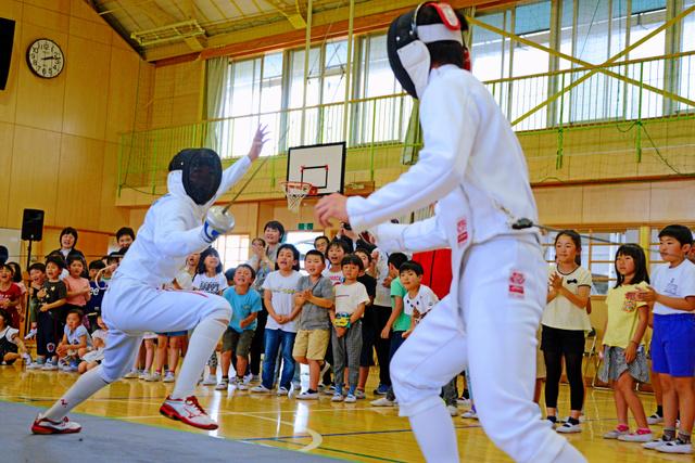 宇津木選手(左)と伊藤選手の試合に児童らは総立ちで応援した=2019年5月10日午後2時12分、千葉県香取市の市立新島小学校、根岸敦生撮影