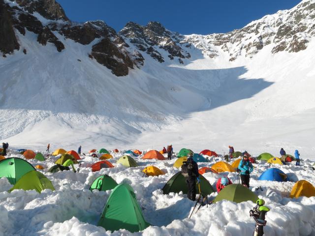 色とりどりのテントが並ぶ穂高連峰の登山基地・涸沢。中央奥のピークは前穂高岳=2019年5月4日午前6時6分、長野県松本市、近藤幸夫撮影