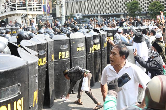 警察が厳戒態勢を敷くなか、大統領選の結果に対する抗議デモをするプラボウォ候補の支持者ら=2019年5月21日、ジャカルタ、野上英文撮影