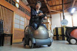 ロデムに乗るテムザックの高本陽一社長=京都市のテムザック中央研究所、田中誠士撮影