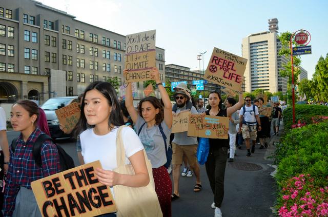 温暖化防止を訴えて官庁街を行進する学生ら=東京・霞が関