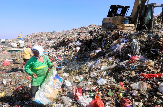 インドネシア・バリ島のごみ集積場で、山積みになったプラスチックごみを回収する業者ら=2018年6月、野上英文撮影