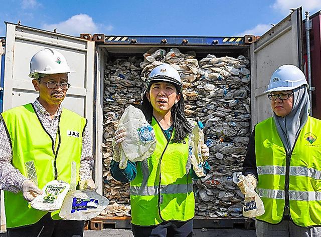 5月28日、クアラルンプール近郊のクラン港で、プラスチックごみの入ったコンテナを報道陣に示すヨー環境相=AFP時事