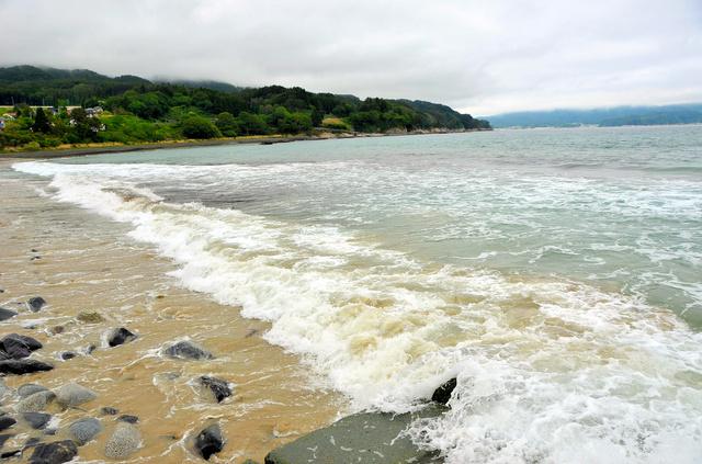 津波と、地盤沈下で砂浜の大半が失われ、岩が目立つ浪板海岸=岩手県大槌町