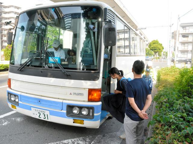 教職員に見守られながら発車する北九州子どもの村小・中学校のスクールバス=北九州市小倉南区