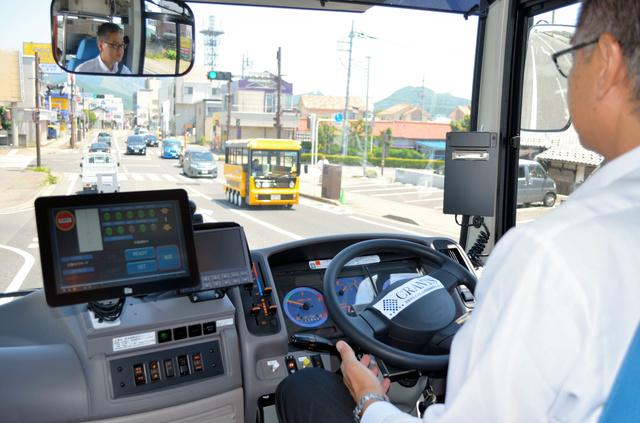 運転手がハンドルから手を離し、自動運転のバスを公道で走らせた。左にある画面で手動と自動を切り替える=2019年5月25日、群馬県桐生市