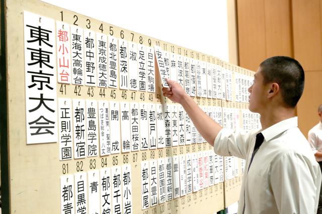 東東京大会の抽選会で、校名が書かれた札を掛ける野球部員=渋谷区、田辺拓也撮影