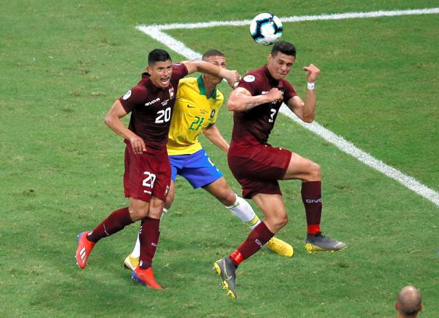 ブラジルの選手(中央)を激しくマークするベネズエラの選手たち=ロイター