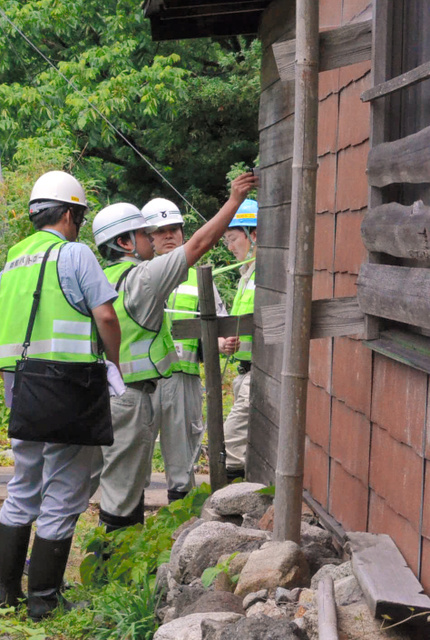 家屋の被害状況を調べる職員ら=2019年6月25日午前、山形県鶴岡市鼠ケ関