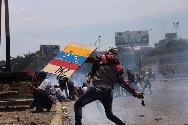 ベネズエラ国旗とスペイン語で「平和」とあしらった板を盾代わりにして、治安部隊に投石して応戦する市民=2019年5月1日、カラカス